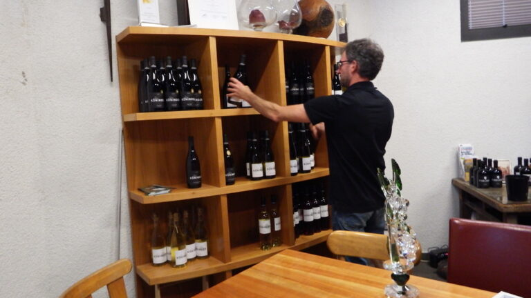 Tobias Köninger in front of his wine shelf