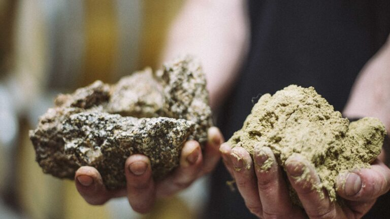 Two hands holding sandy soil and a granite stone.