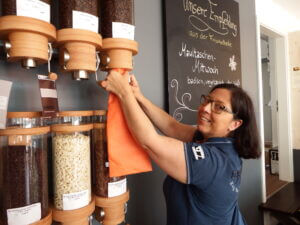 Carmen Blust demonstrates the use of a refill bag at a coffee refill station.
