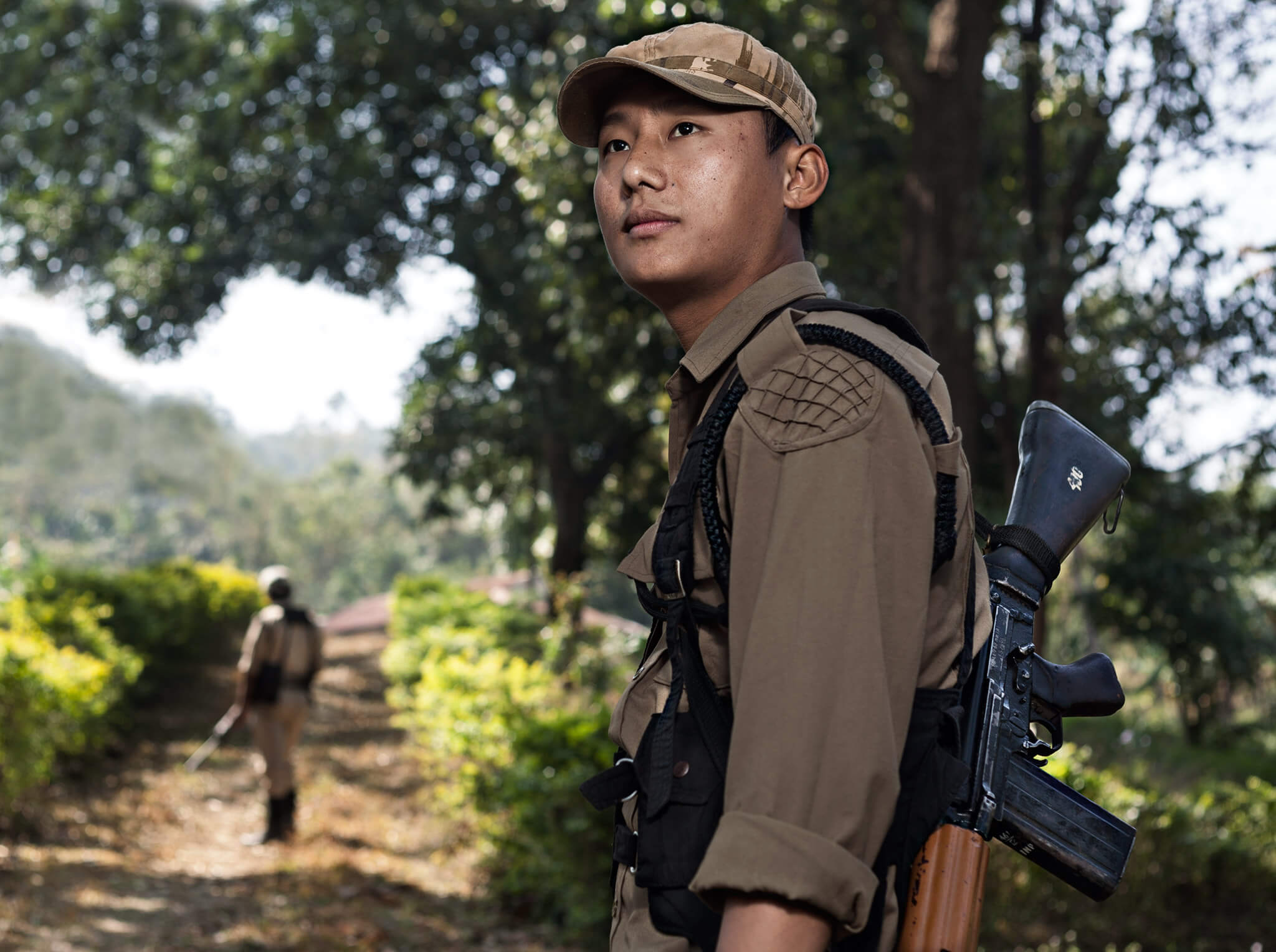 A forest ranger in India is looking towards the right and is in a forest in India