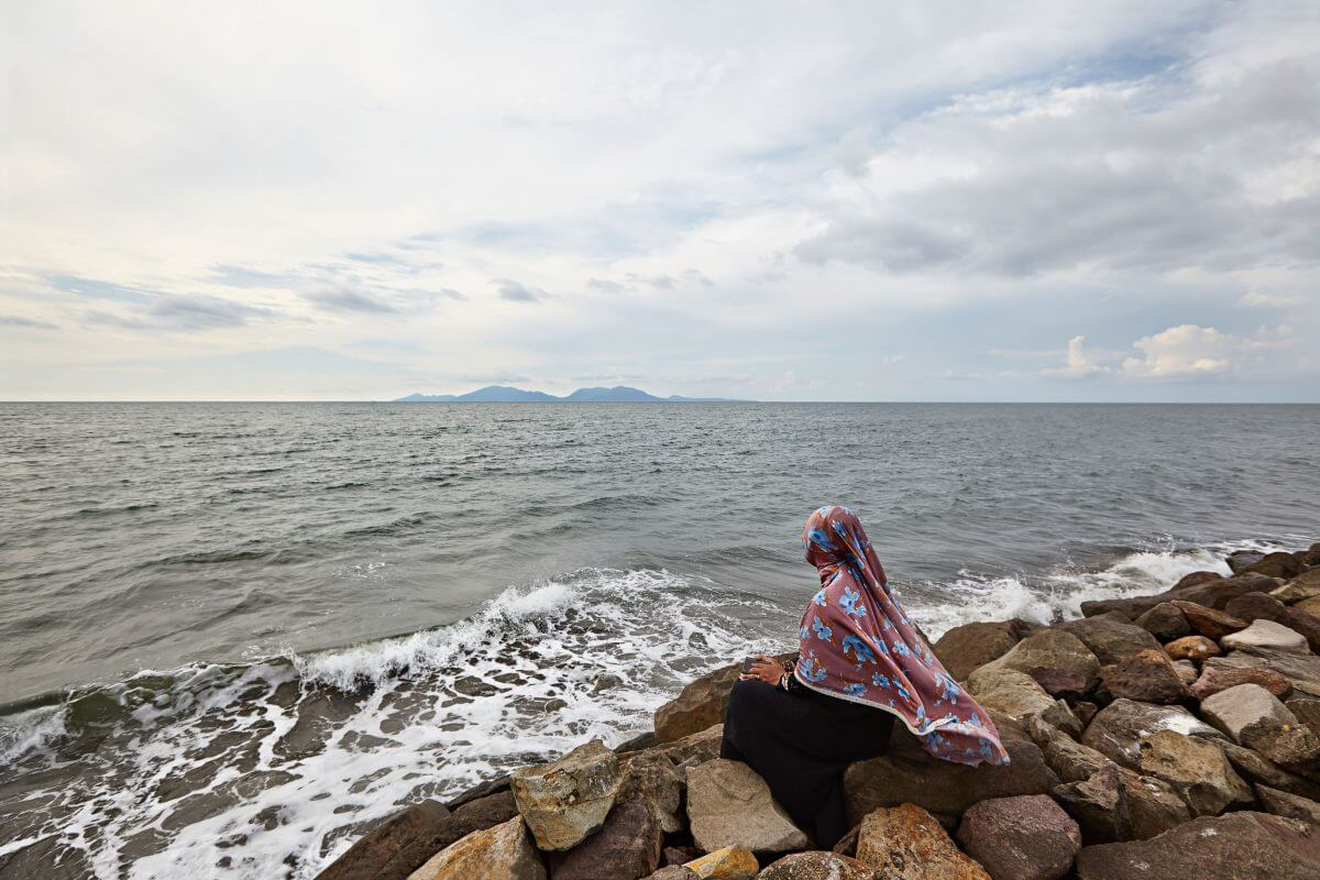 woman gazes out at the Indian Ocean from the Indonesian province of Aceh, nearly 15 years after a tsunami devastated the region.