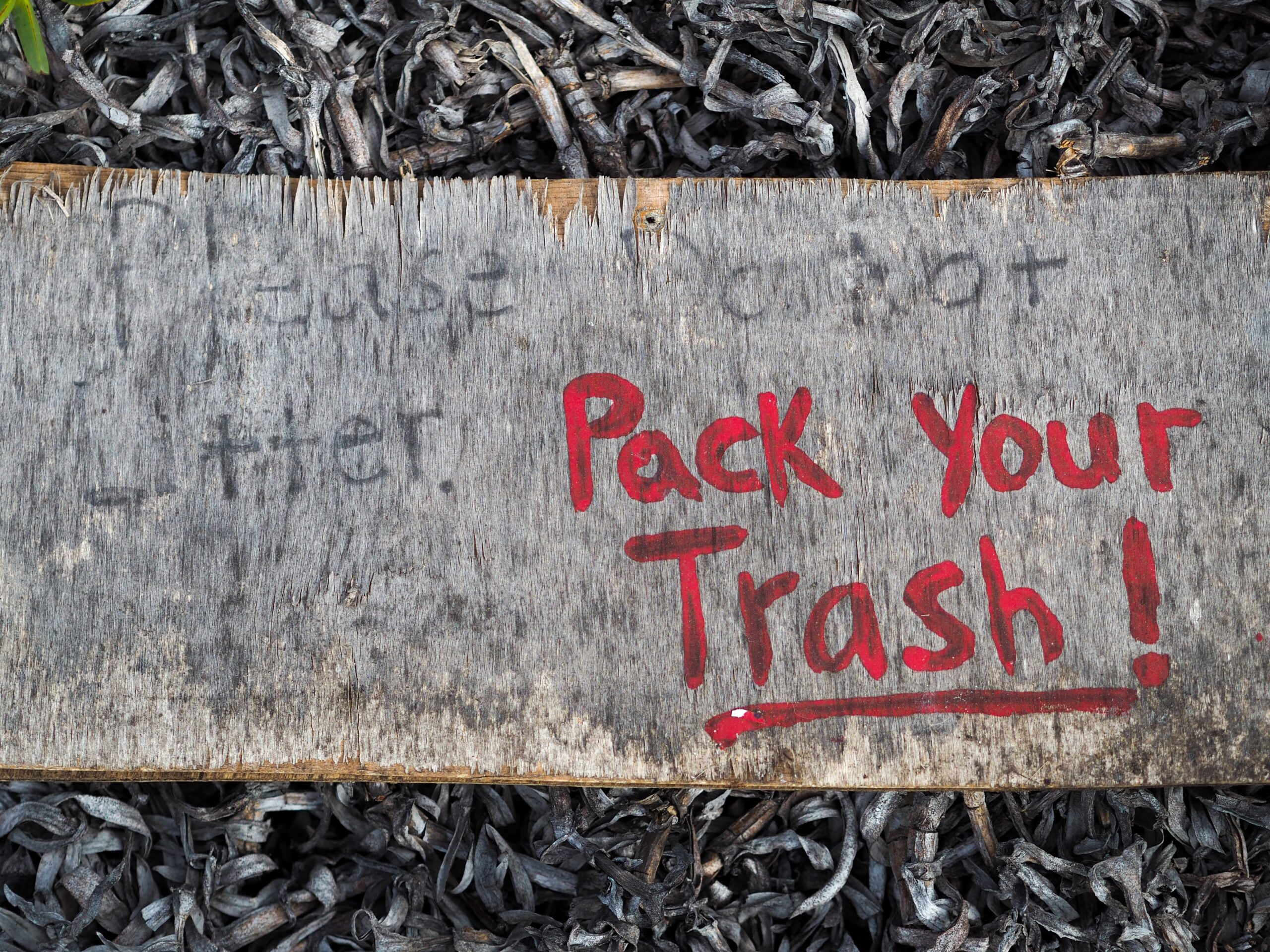 """Pack Your Trash"" is written in red on a piece of wood."