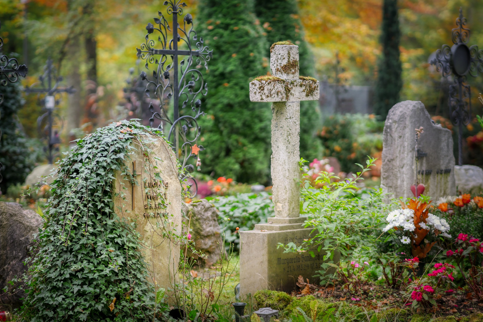 A picture of a stone cross and grave stone.