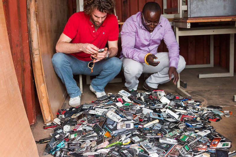 Two men in front of collected phones.