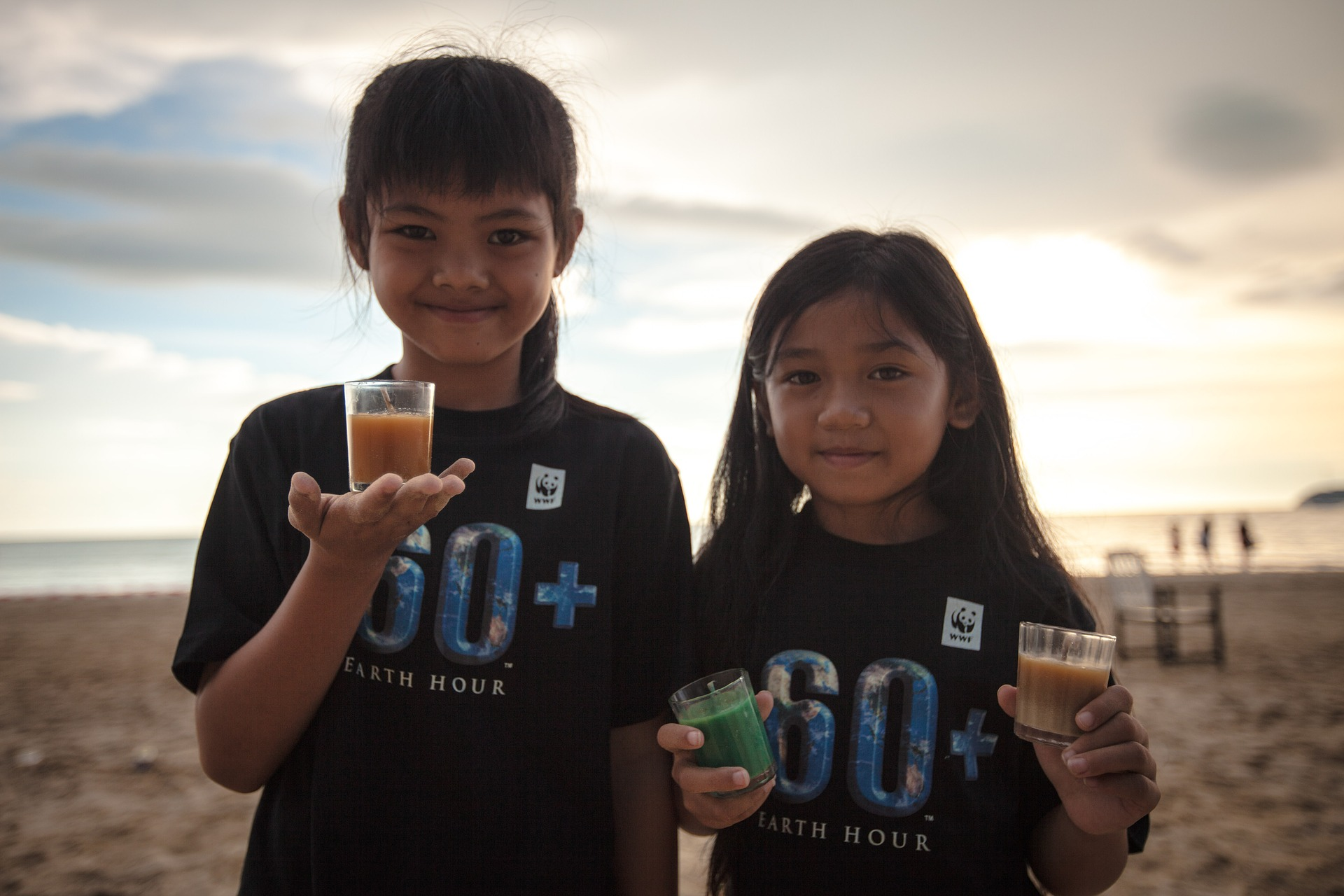 Two young girls holding glasses with smoothie and wearing Earth Hour shirts.
