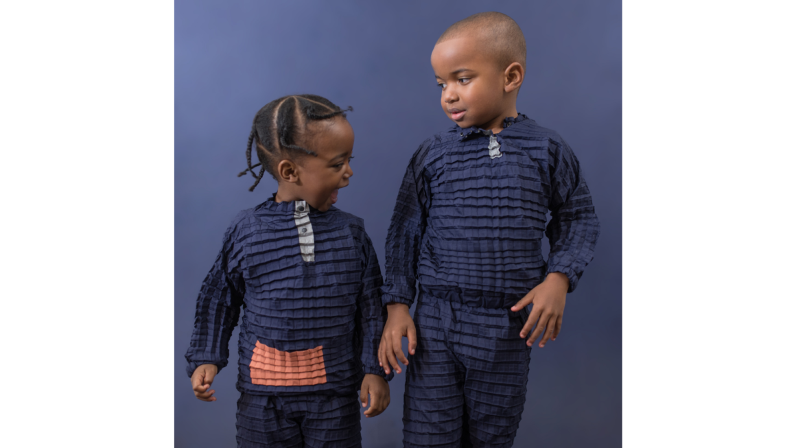 Petit Pli makes sustainable clothing that grows with your kid. The image has two kids - one boy and one girl - wearing blue petiti pli's garments