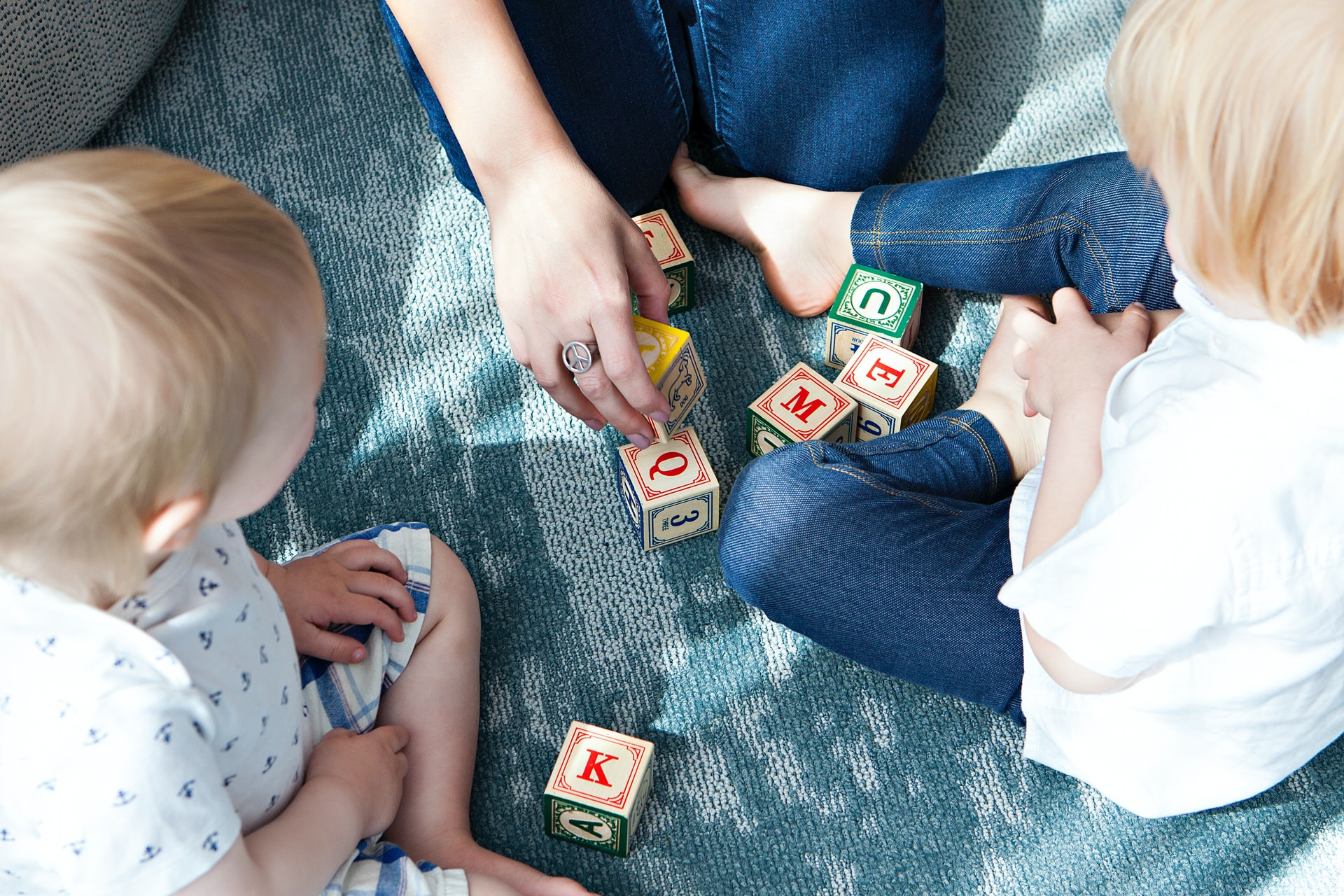 A woman is playing with wood blocks with two children.