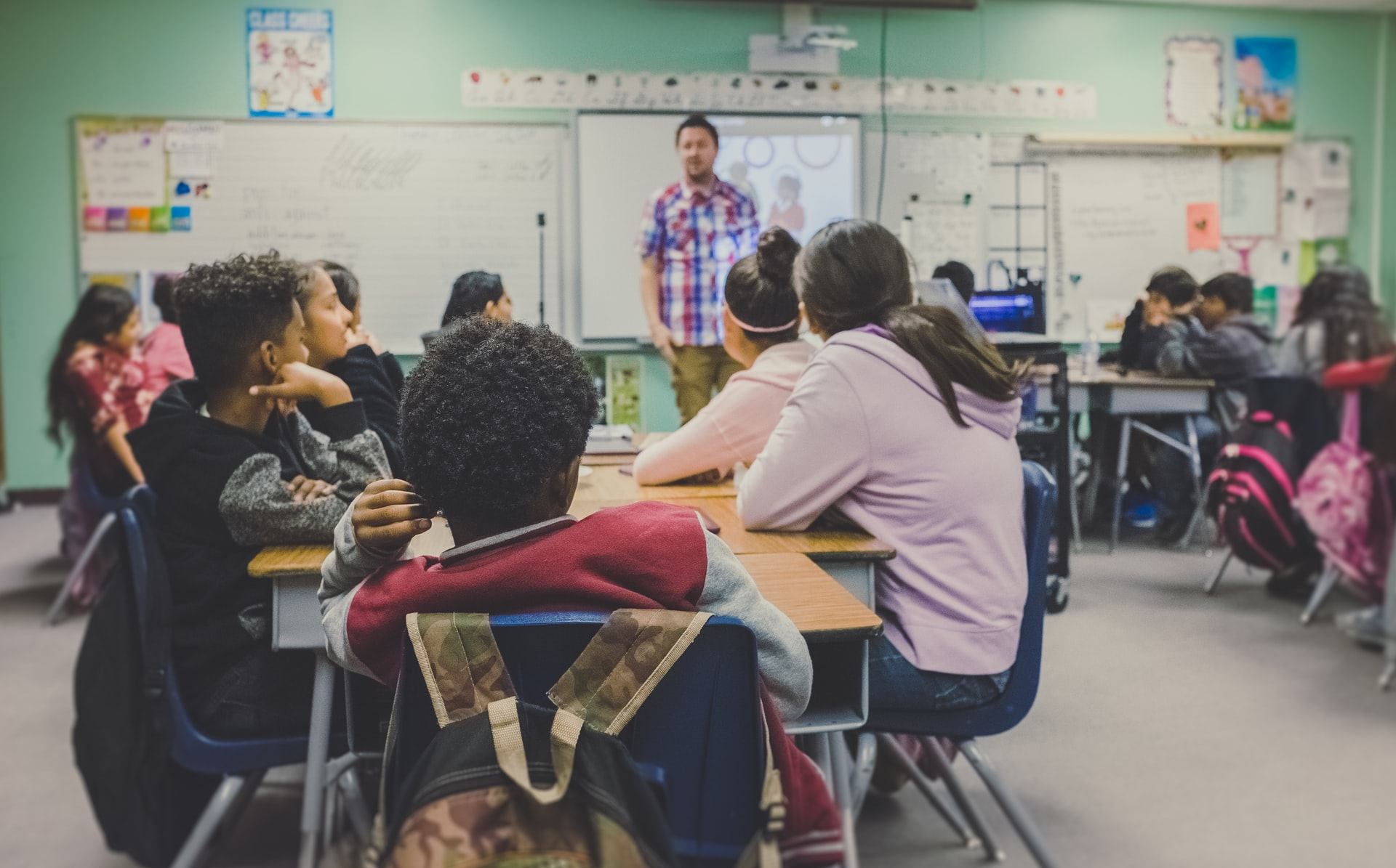 A man teaches teenagers in a classroom.