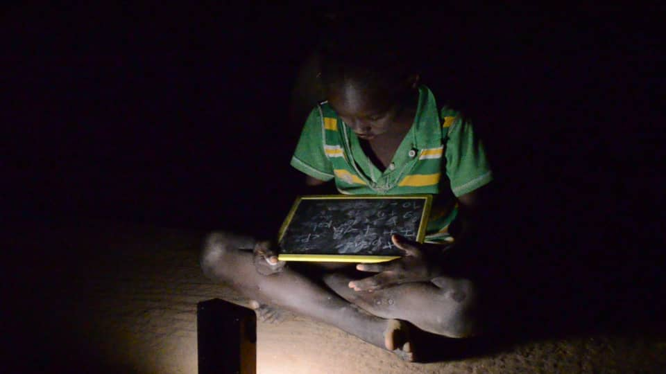 A kid using the lamp to read at night. Photo: Claire