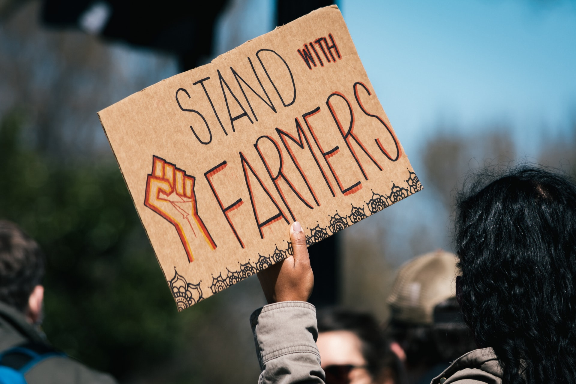 """Protest sign reading """"stand with farmers"""""""